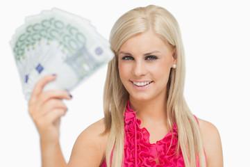 Fair hair woman holding 100 euros banknotes
