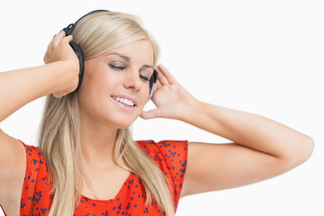 Happy blonde in orange dress listening to music