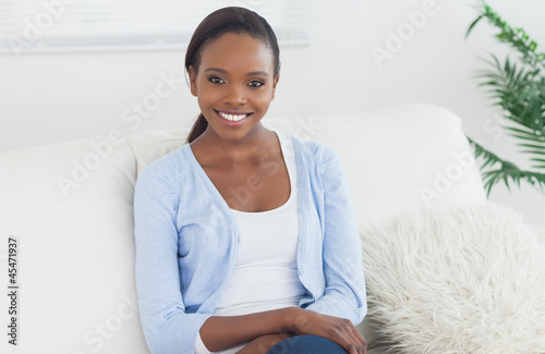 Black woman sitting on a sofa looking at camera