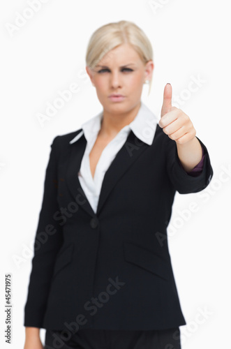 Serious blonde businesswoman thumb-up