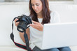 Woman holding a laptop and a camera