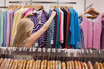 Woman searching clothes at the clothes rack