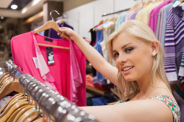 Woman is standing at a clothes rack and looking at clothes