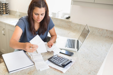 Woman calculating bills with laptop