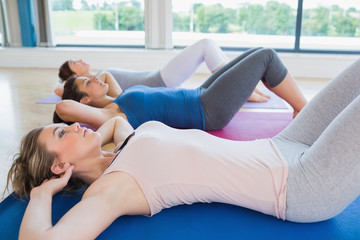Women doing sit ups on exercise mats