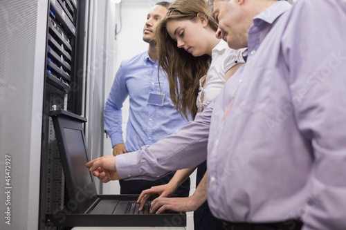 Technicians checking servers with laptop