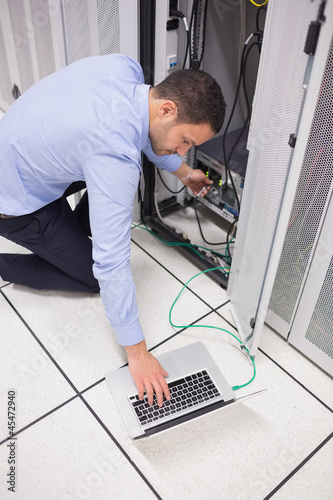Technician connecting his laptop to server