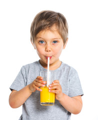 Portrait of little boy drinking orange juice
