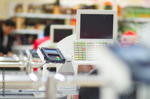 Multiple cash-desks with cashier and terminal in supermarket