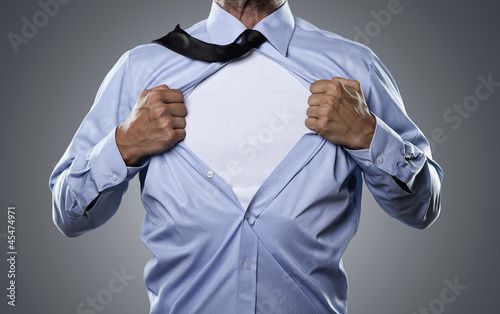 Superhero, young businessman tearing his shirt off