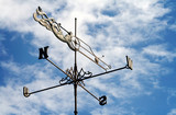Weather vane against a cloudy blue sky