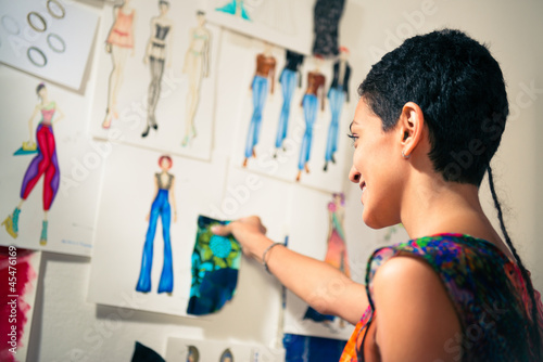 Female fashion designer contemplating drawings in studio - 45476169