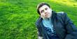 Красивый молодой мужчина лежит на траве в парке