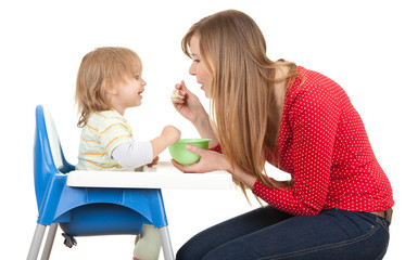 mom giving food to her son on high chair vertical shape