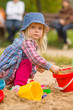 Adorable girl in dress and hat play on sandbox on playground