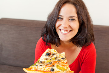 Cheerful woman eating a pizza