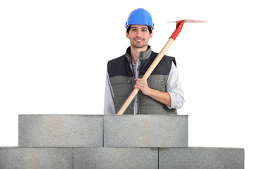 Man with shovel behind concrete wall