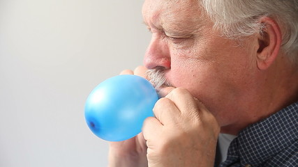 senior man blows small balloon till it pops