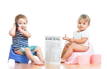 funny children with newspaper and pda on chamberpot