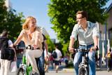 Paar in Stadt fährt mit Fahrrad in Freizeit