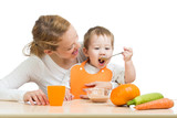 baby eating vegetables puree by spoon himself and sitting on mot