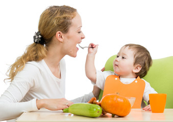 playful baby spoon feeding his mother isolated on white