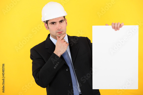A pensive architect holding a poster.