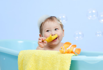 adorable baby taking bath in blue tub