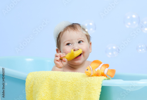 adorable baby taking bath in blue tub