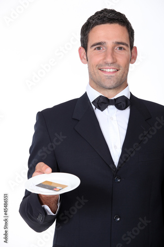 A waiter presenting a credit card.