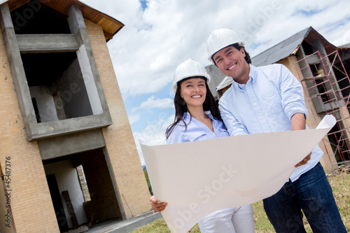 Couple holding blueprints