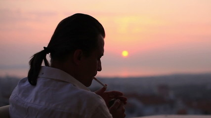 man watching sunset and smoke cigarette