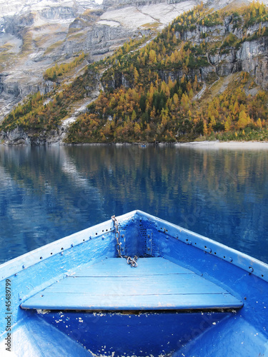 Prow of a boat against surface of Oeschinen lake and Alps
