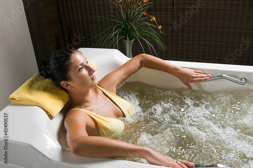 Beautiful young woman relaxing in jacuzzi