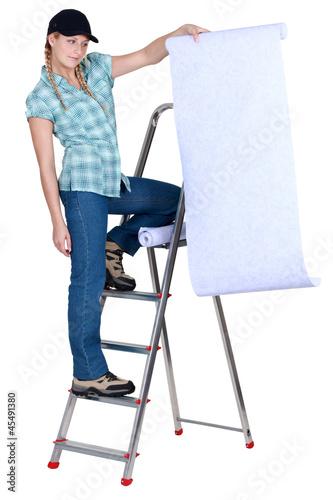 Women spreading roll of wallpaper