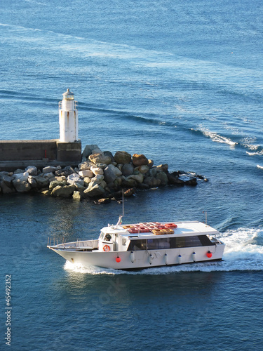 Pleasure boat entering port of Camogli, Italy