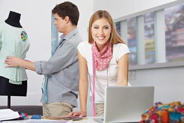 Modedesigner im Atelier mit Laptop