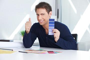 Designer mit Farbfächer halt Daumen hoch