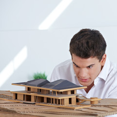 Architekt betrachtet Hausmodell