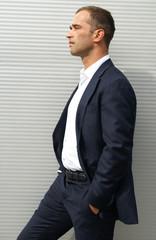 Man posing against a striped wall