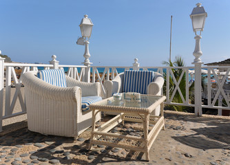 Two cane armchairs and a table on the terrace against Atlantic.