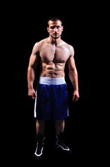 Powerful muscular boxer posing on black background