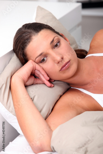 Brunette woman lying in bed