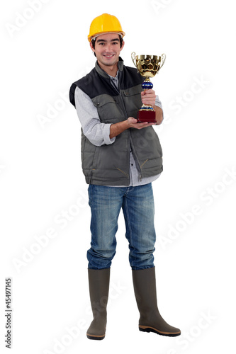Builder holding trophy