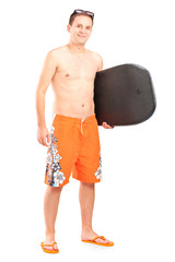 Male surfer posing with his surfboard