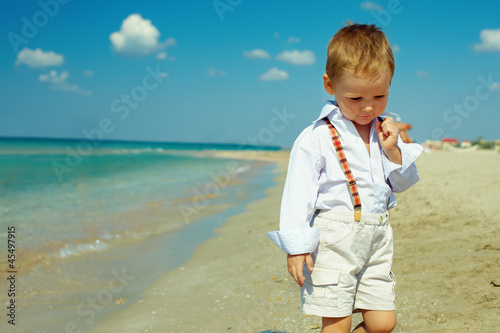 dreamy baby boy walking the sea beach