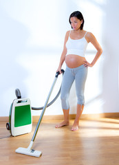 Beautiful pregnant woman retro vacuum housewife