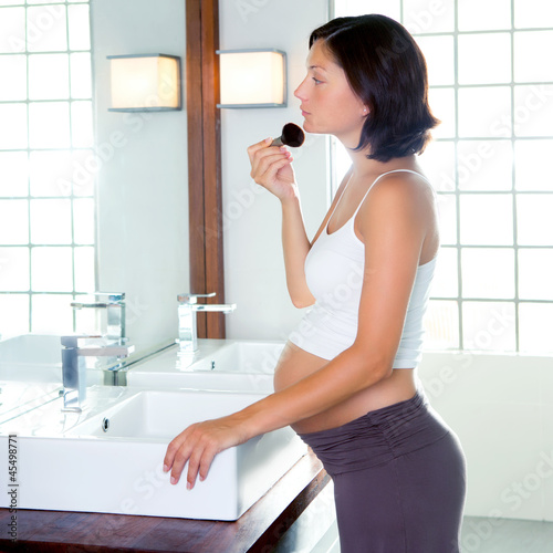 Beautiful pregnant woman on modern bathroom makeup