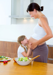 Beautiful pregnant mother with her daughter at kitchen