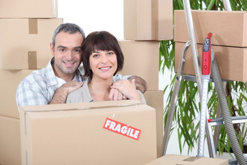 Couple stood by packed boxes